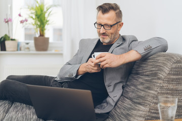 Man using laptop while having coffee on sofa