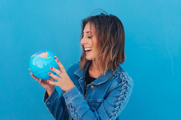 Laughing happy woman holding a world globe