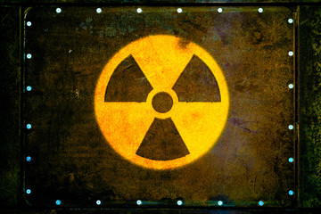 Round yellow radioactive (ionizing radiation) danger warning symbol painted on massive rusty metal plate fixed with metallic rivets to the wall with dark rusty brown and green moss.