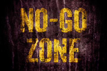"""No-Go Zone"" warning sign in yellow letters painted over dark grungy concrete wall texture background. Sign as concept for: do not enter the area, caution, danger or off limits in violent urban areas"