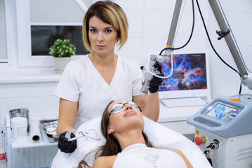 Women doctor in clinic. Beautiful female face and cosmetologist's hands with syringe during facial beauty injections. Rejuvenation and hydratation. Cosmetology concept