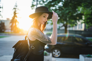 Creative redhead woman in gothic black dress and hat in the city. Street style
