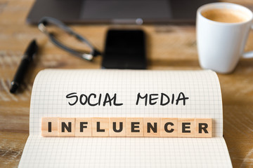 Closeup on notebook over wood table background, focus on wooden blocks with letters making Social Media Influencer text