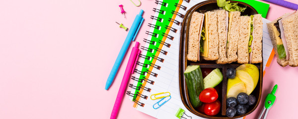 Overhead shoot with wooden lunch box with sandwiches, vegetables and fruits on pink background and school stationery. Healthy children eating concept. Top view with copy space. Banner.