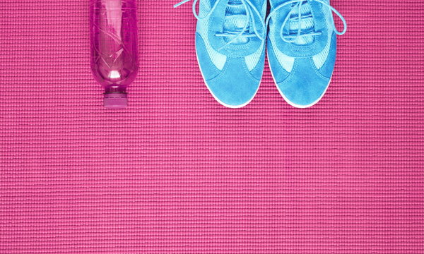 Light blue sneakers and water bottle on pink background of yoga mat. Concept of healthy lifestile. Flat lay, top view, copy space