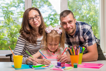 Mom and Dad help their little girl do homework for school
