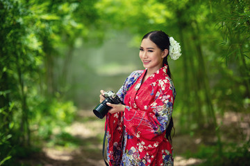 Japanese woman wearing a kimono is shooting with a camera.