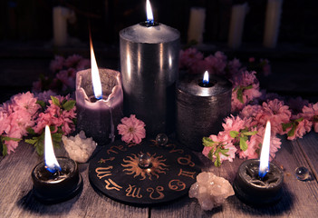 Black candles and zodiac circle with sakura flowers on witch table. Occult, esoteric and divination still life. Halloween background with vintage objects