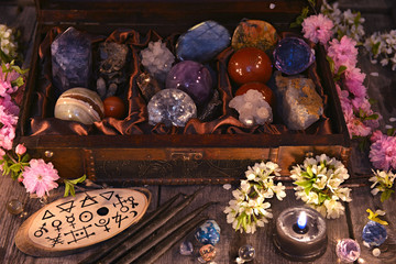 Box with magic crystals and stones, black candle and spring flowers. Occult, esoteric and divination still life. Halloween background with vintage objects