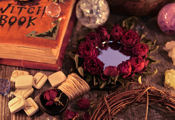 Close up with magic mirror, witch book and runes on the table. Occult, esoteric and divination still life. Halloween background with vintage objects