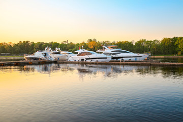 Luxury yachts docked in marina at colorful sunset. Marine parking, modern motor boats moored in water bay at pier. Summer view of river bank, embankment and superyachts in sunshine. Sunny evening.