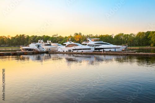 Luxury yachts docked in marina at colorful sunset  Marine