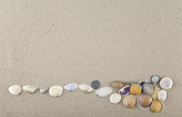 Seashells and stones on sand for relaxation as a background