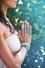 close up of yoga woman hands in namaste gesture with lot of boho style jewelry rings and bracelets outdoor