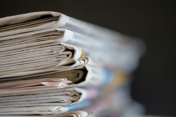Newspapers folded and stacked with black background, selective focus.
