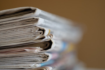 Newspapers folded and stacked with brown background, selective focus.