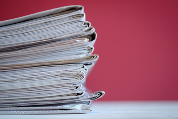 Newspapers folded and stacked with red background, selective focus.