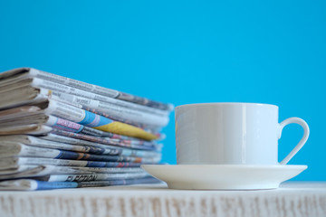 Newspapers folded and stacked with blue background, selective focus.