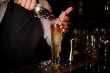 Barman adding an ice into the summer cocktail