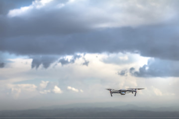 Drone quadrocopter with high resolution digital camera flying on the cloudy thunder sky