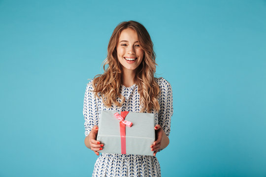 Happy blonde woman in dress holding gift box