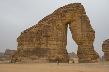 Locals standing in the giant arch of Elephant Rock, Al Ula, Saudi Arabia, Middle East