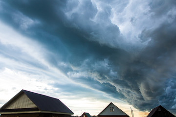 Stormy clouds over a small town with one-story houses. Formation of a hurricane
