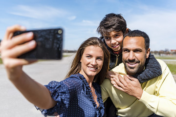 Happy family taking a selfie outdoors