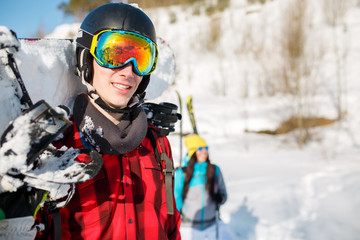 Picture of young man wearing helmet with snowboard