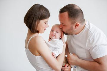 Photo of cuddling parents with newborn son