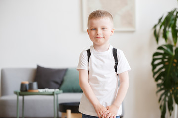 Image of boy in white T-shirt with backpack on background of sofa