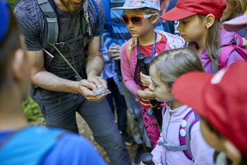 Man and kids with magnifying glass on a field trip