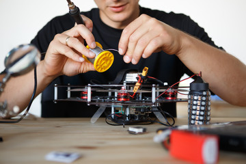 Photo of engineer with soldering iron repairing mechanism
