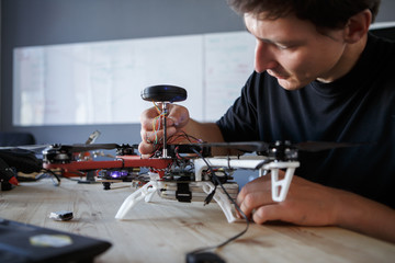 Photo of engineer fixing square copter at table