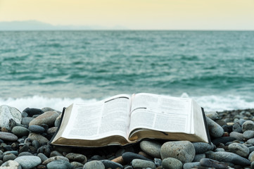 Bible open on top of small stones in front of the green sea and an orange sky. Copy space.