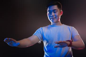 Virtual panel. Pleasant young man looking at his hands while using a virtual panel