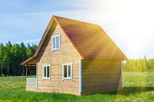 Деревянный дом с крыльцом на лугу, на фоне зелёных деревьев и голубого неба с солнечными лучами