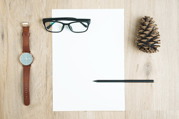 Blank a4 paper on top of wood table with black pencil, pinecone, watch and glasses.