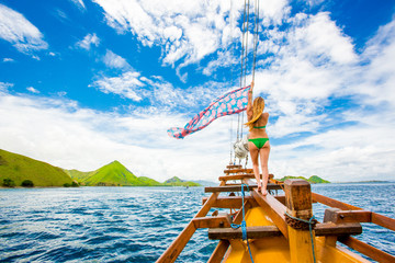 Girl perched on bow of Phinisi Boat, sailing through Komodo National Park, Indonesia, Southeast Asia, Asia