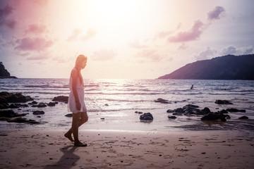 silhouette girl walk on the beach, foot print on sand texture.