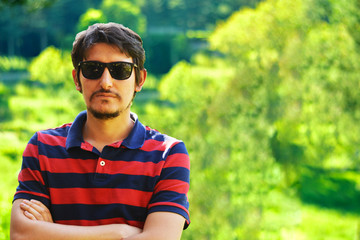 Young man outdoors portrait looking at the camera with natural green background. Neutral Facial Emotion.