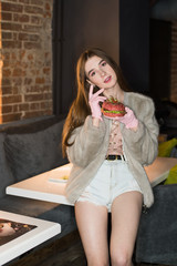 Beautiful, sexy girl eating a burger. Concept. weight loss. Pink vegetarian burger. Fashion advertising concept.