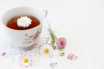 Cup of tea with daisies on white background