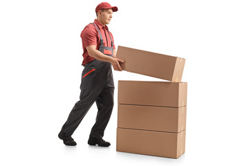 Full length profile shot of a mover placing a package on top of a stack