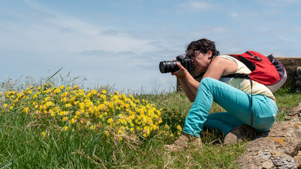 female photographer taking a photograph, outdoors