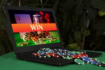 "A lot of poker chips on the laptop with the inscription ""win"""