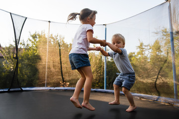 Adorable siblings bouncing together on trampoline