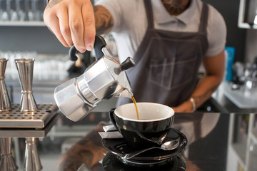 Barista pours coffee from the coffee pot inside contemporary design style cafe with bar