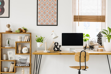 Real photo of a desk with a computer screen, lamp and ornaments standing with a chair next to a shelf with more ornaments in a work room with posters on a wall and window with blinds
