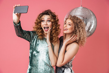 Two beautiful happy women in shiny dresses